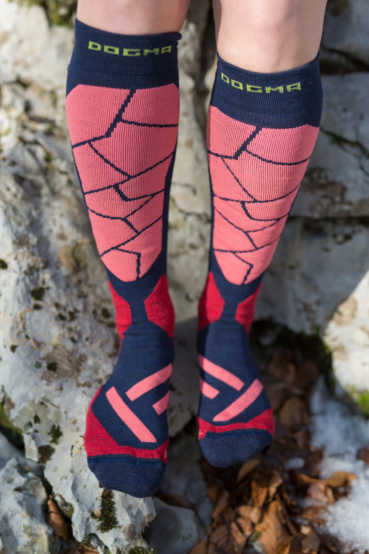 This is a picture of Dogma Snow Eater winter socks, knee height for women. Socks are in mosaic print, color is named Shield purple. Colors are dark purple, salmon and red.