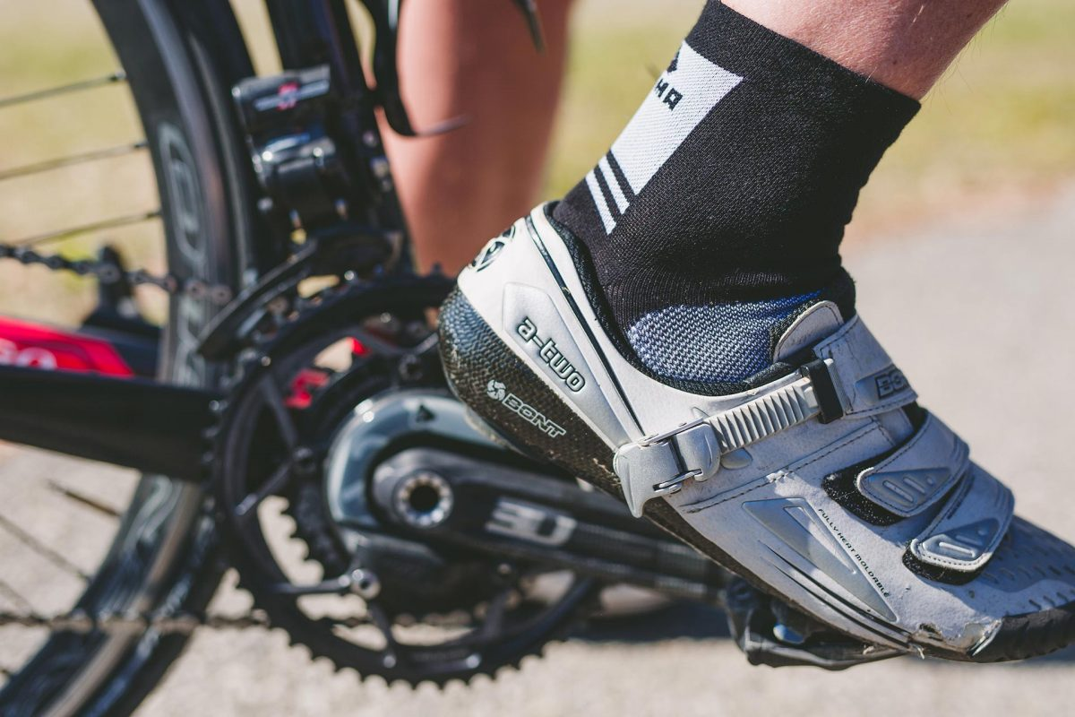 A side picture of a man wearing dogma shifter biking socks in blk and white