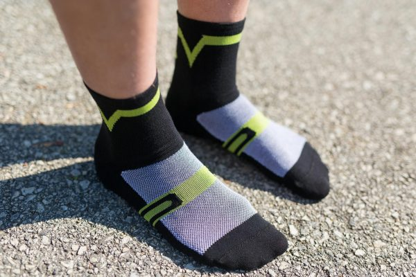 Front feet picture of a man wearing dogma velocity blk and green biking socks showing front design and structure