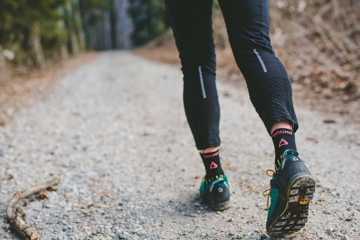This is a picture of a woman walkinh in the woods wearing dogma mountain goat hiking socks in blacks. It is taken from behind showing dogma logo in salmon