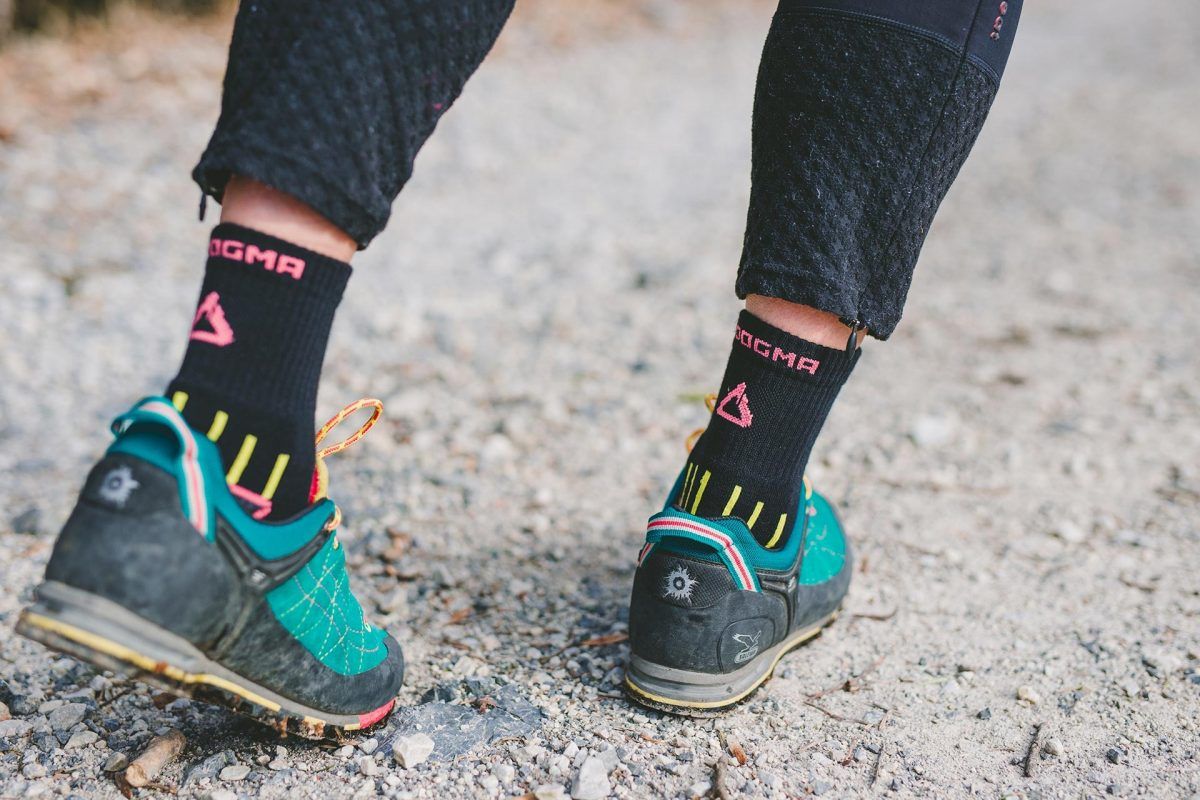 This picture is showing a woman wearing dogma mountain goat socks in black color. Picture is showing back design of socks