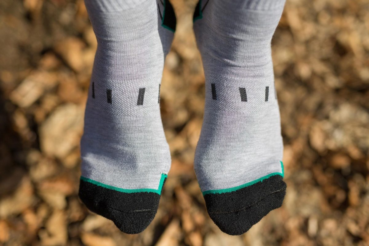 Front feet picture of a man wearing dogma mountain goat socks in grey color with black and green stripes. Picture is taken in the woods