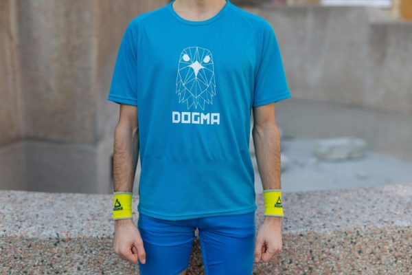 A close up picture of a man wearing Dogma run Falcon t-shirt in blue with white Dogma sign and falcon head print on front. Man is wearing yellow Dogma wrist bands on both hands.