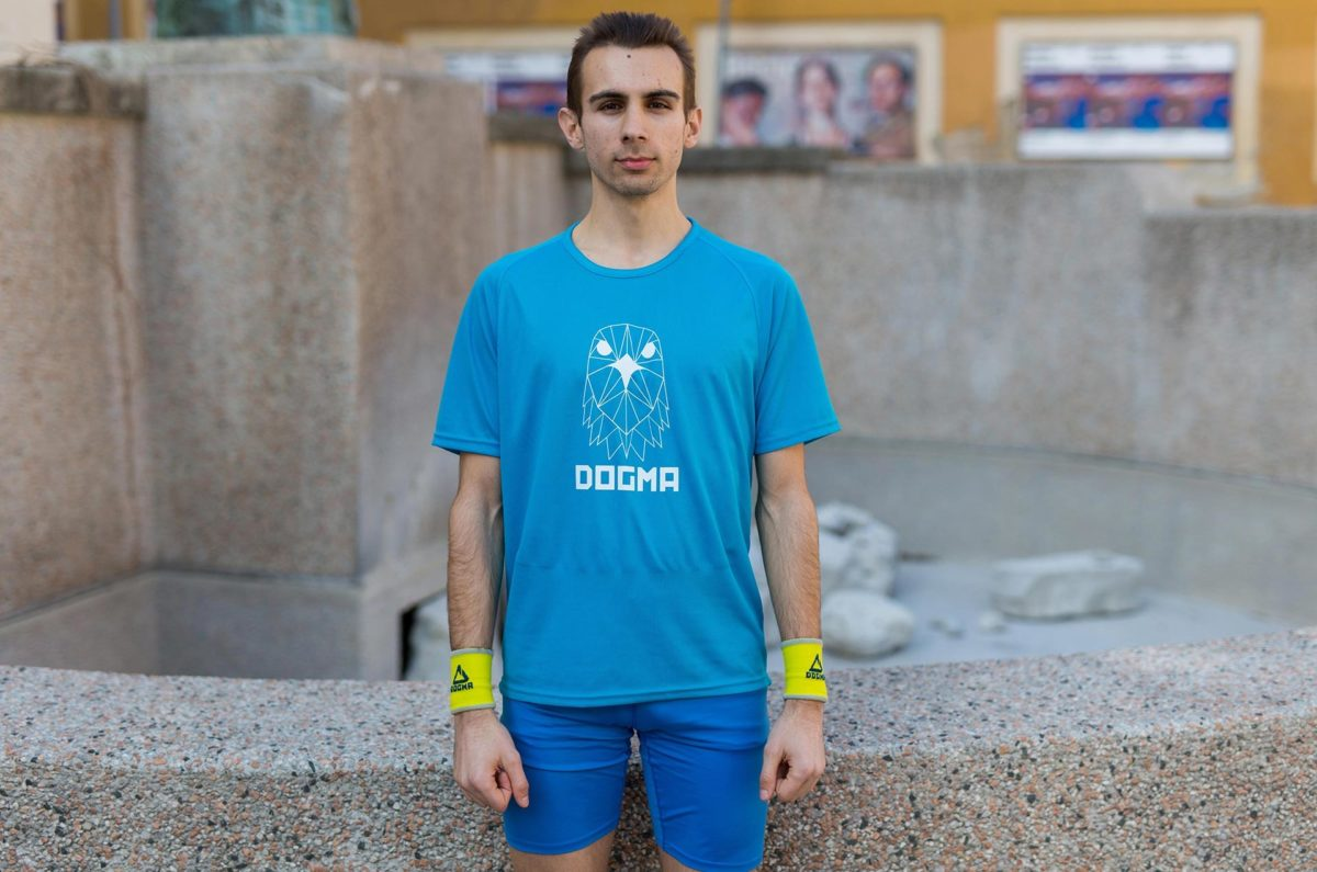 A picture of a man wearing Dogma run Falcon t-shirt in blue and yellow Dogma wrist bands.