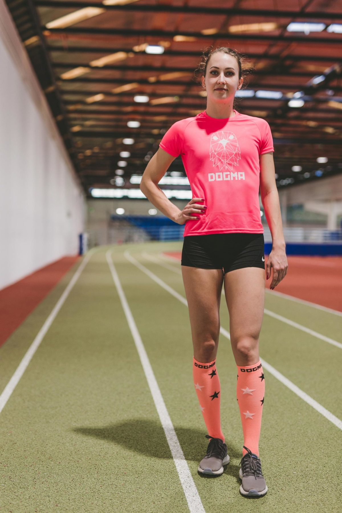 A picture of a girl wearing Dogma Falcon run t-shirt in salmon and Dogma Gazelle woman running socks, knee height in salmon with white and black stars.