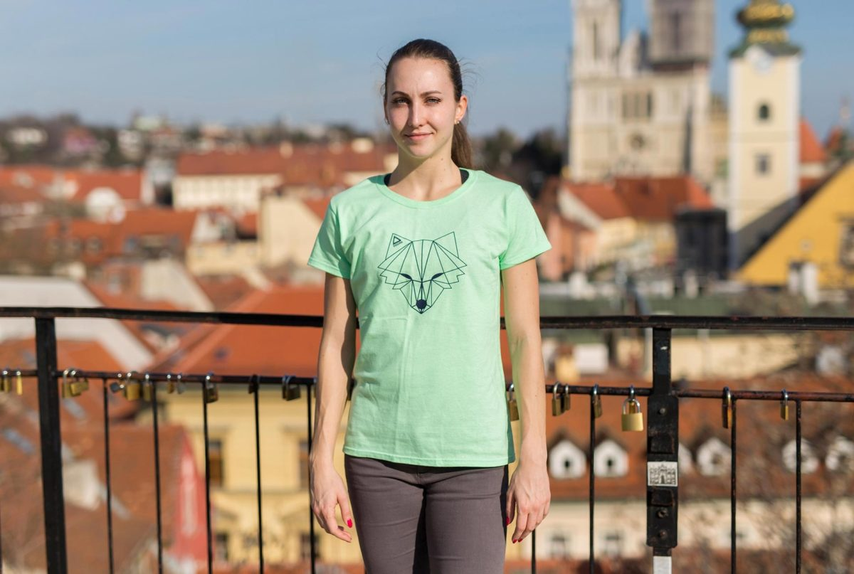 A picture of a girl wearing Dogma run fox t-shirt in green.