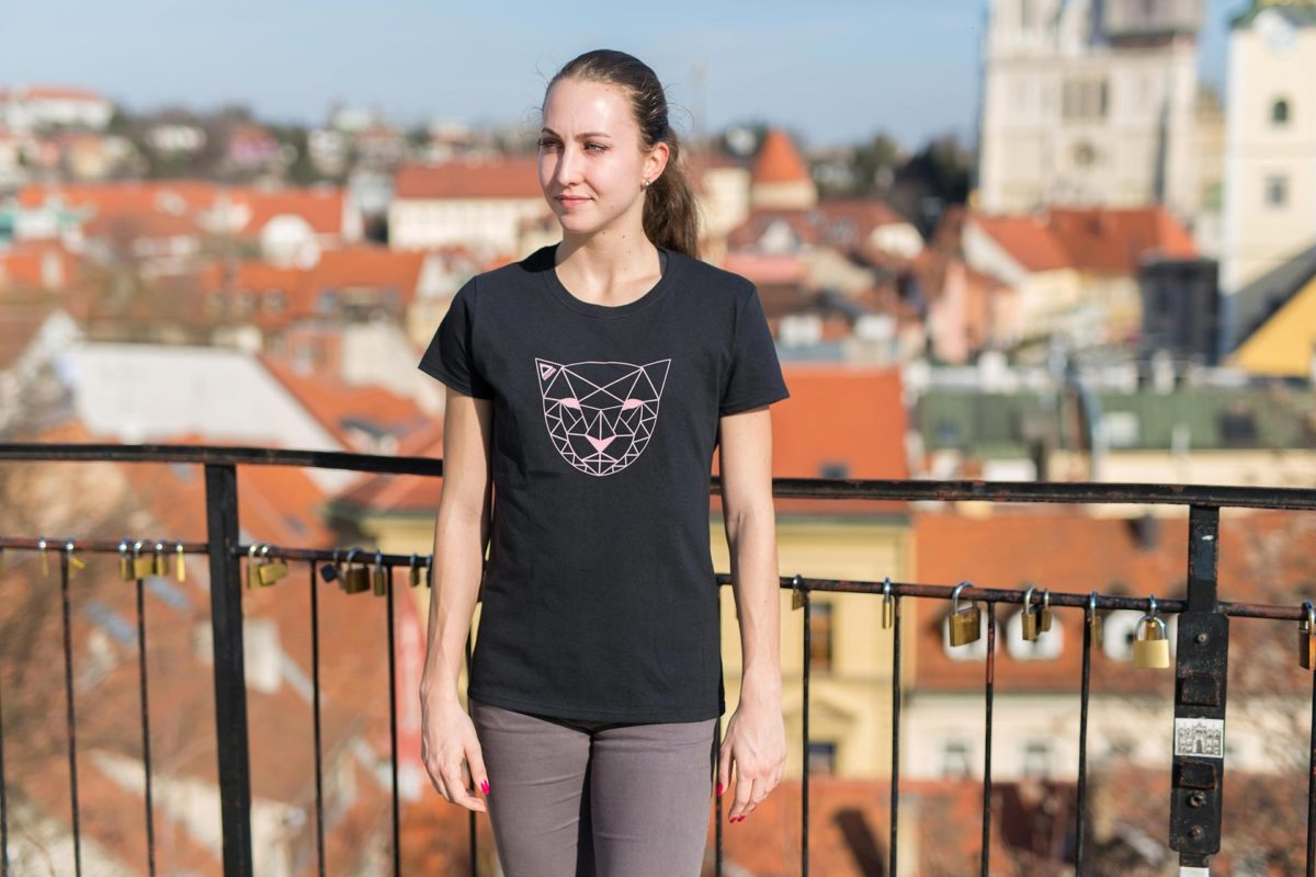 A picture of a woman wearing Dogma run Mountain Lion t-shirt in black. Picture is taken in a standing position in Zagreb.