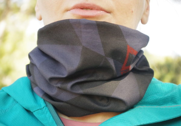 A close up picture of a woman wearing Dogmasocks run neckwarmer in black mamba.