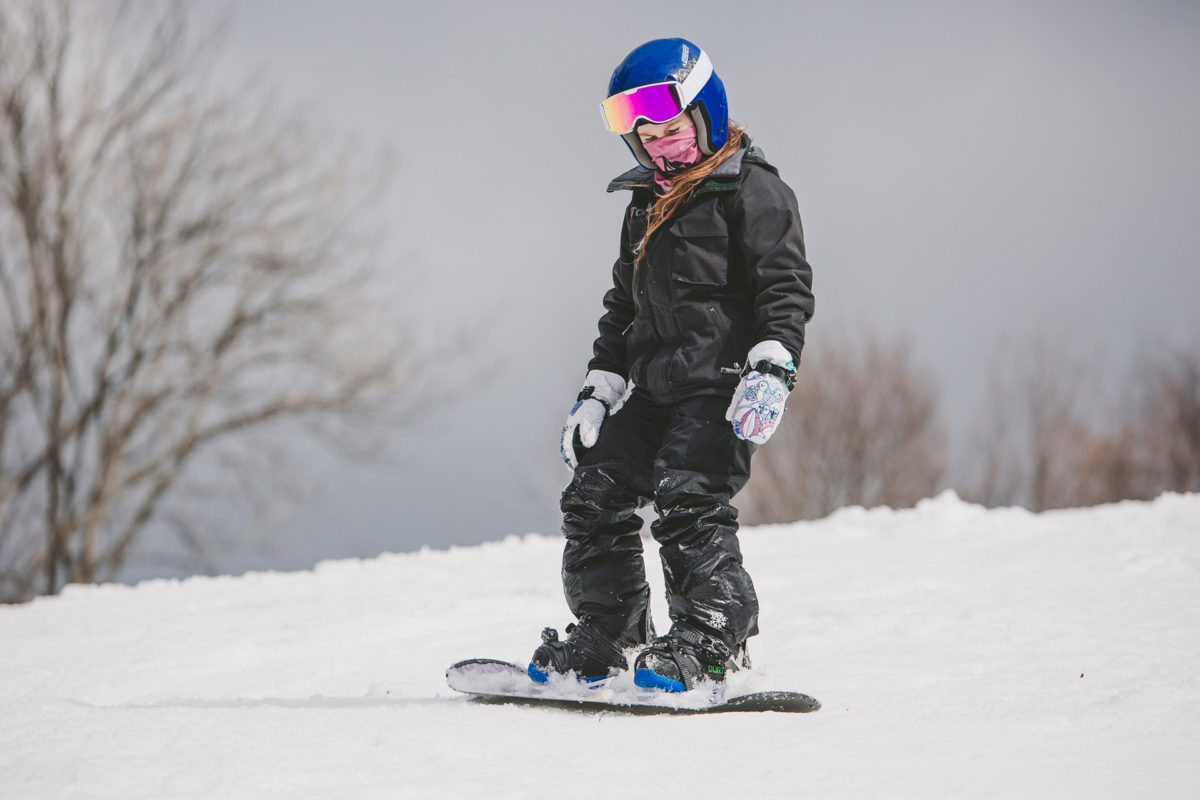 A picture of a little girl on her snowboard wearing pink marble Dogma neckwarmer.