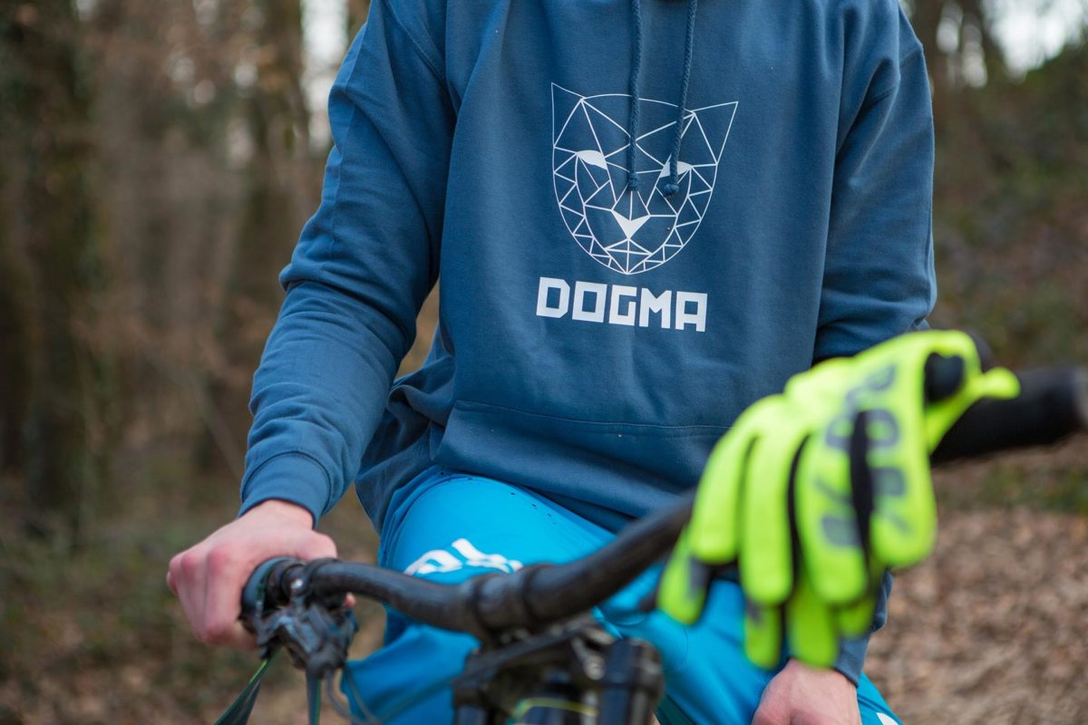 A picture of a man riding bike and wearing Dogma Snow Mountain Lion hoodie in dark grey. Picture is taken in the woods.