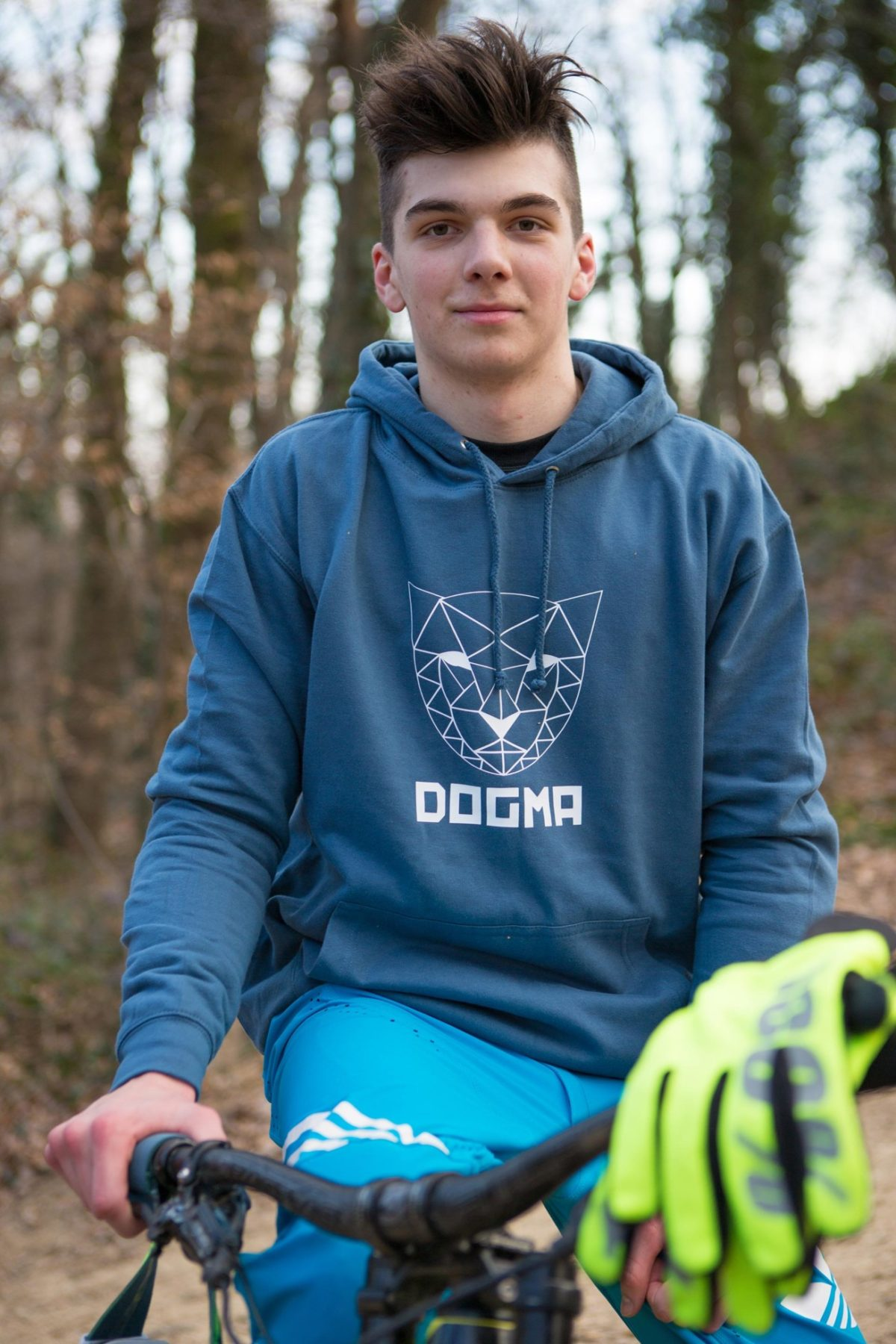 A picture of a boy riding bike and wearing Dogma Snow Mountain Lion hoodie in dark grey. Picture is showing a boy sitting on his ride and smiling.