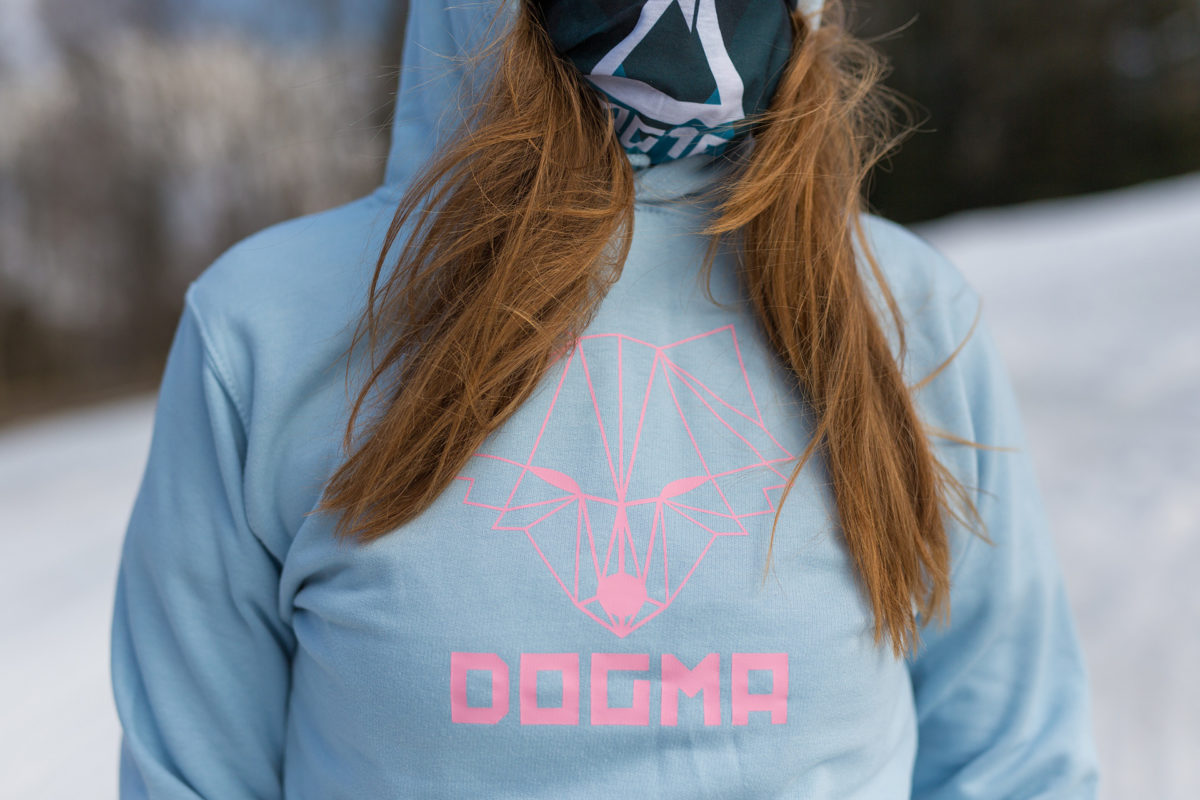 A picture of a girl wearing dogma hoodie in baby blue with printed fox and Dogma sign in pink color. Close up picture with bandana.