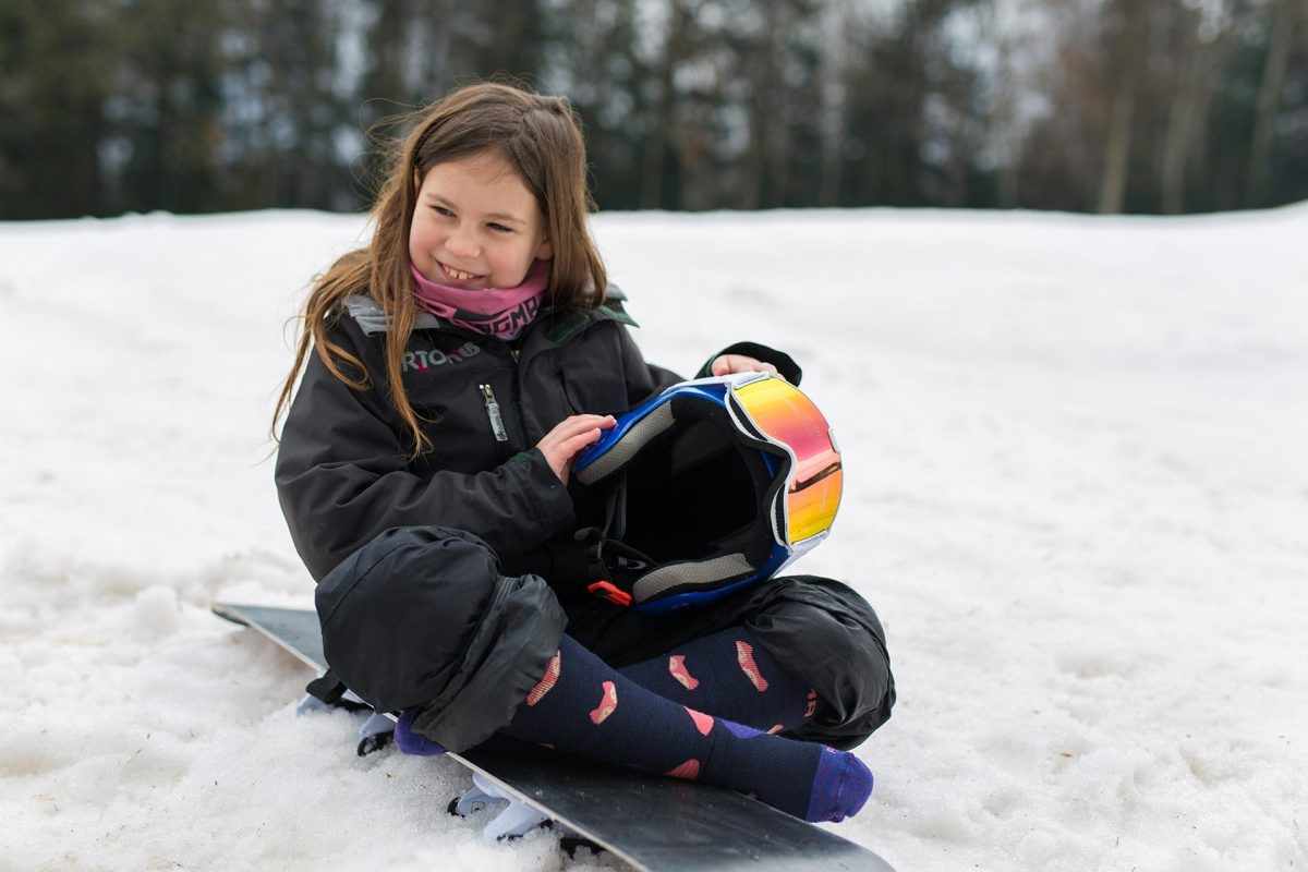 This picture is showing a girl sitting on her snowboard and wearing Dogma Snow Fox junior in blue color.