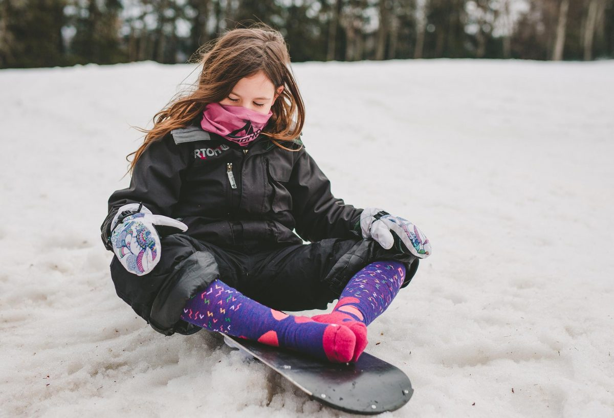 A picture of a girl sitting on her snowboard wearing snow fox junior socks and pink neckwarmer