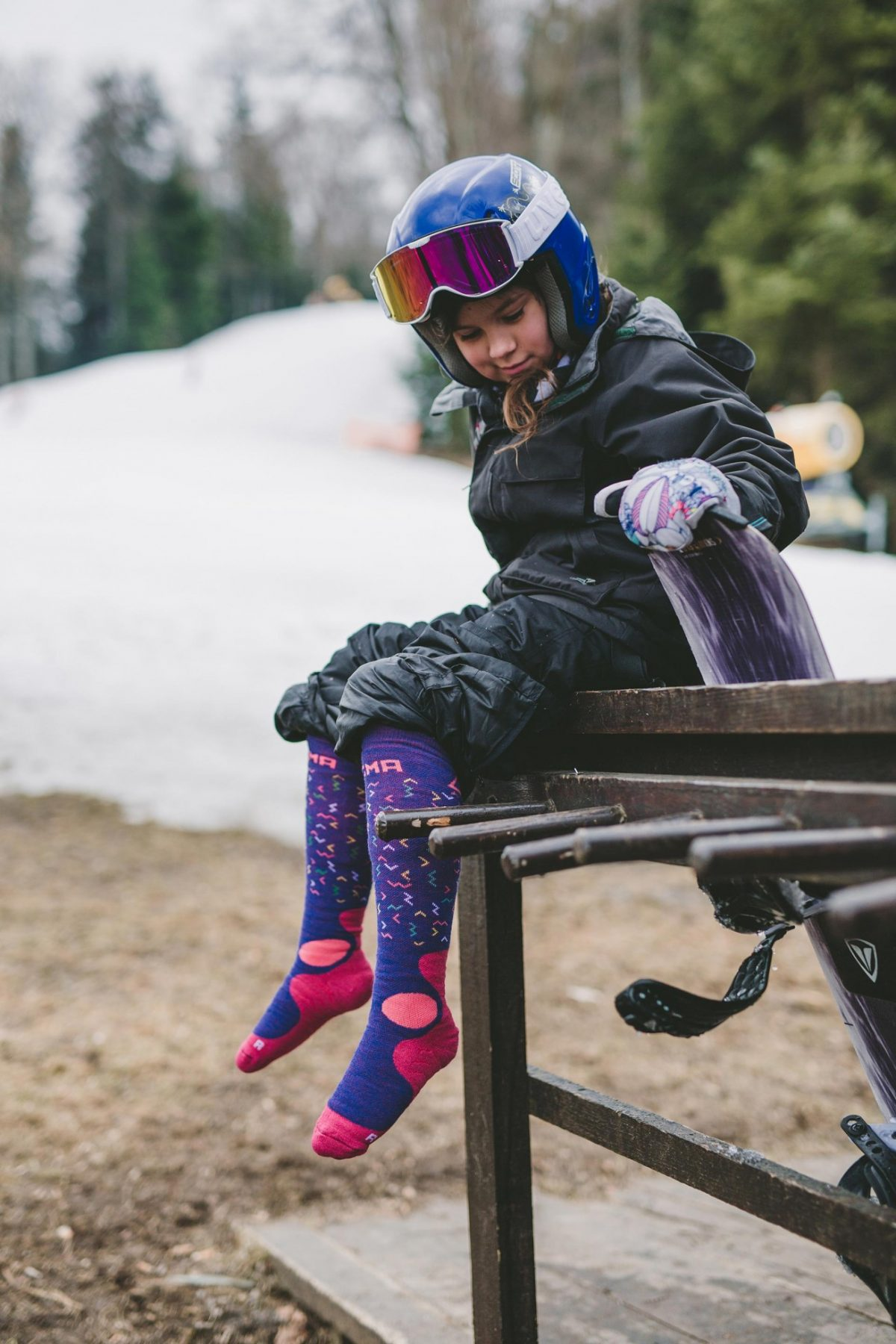 A picture of a girl sitting and wearing dogma junior fox worms socks in purple