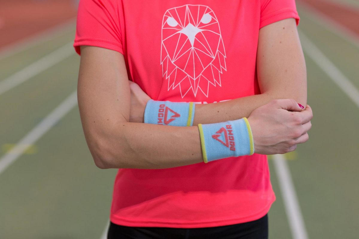 Close up picture of a woman wearing Dogma run falcon t-shirt in salmon and Dogma baby blue wrist bands on both hands with yellow stripes and salmon dogma sign and logo.
