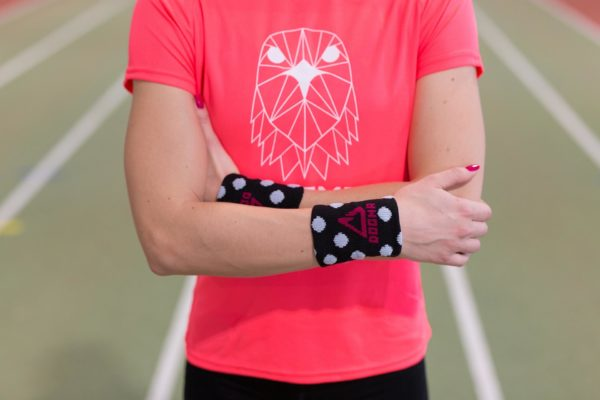 A picture of a girl wearing dogmasocks sweatbands on both hands in black with white dots.