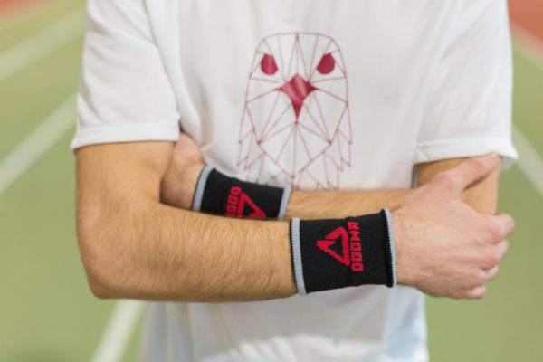 A picture of Dogmasocks wrist sweatband man in black with white stripe and red Dogma logo and sign