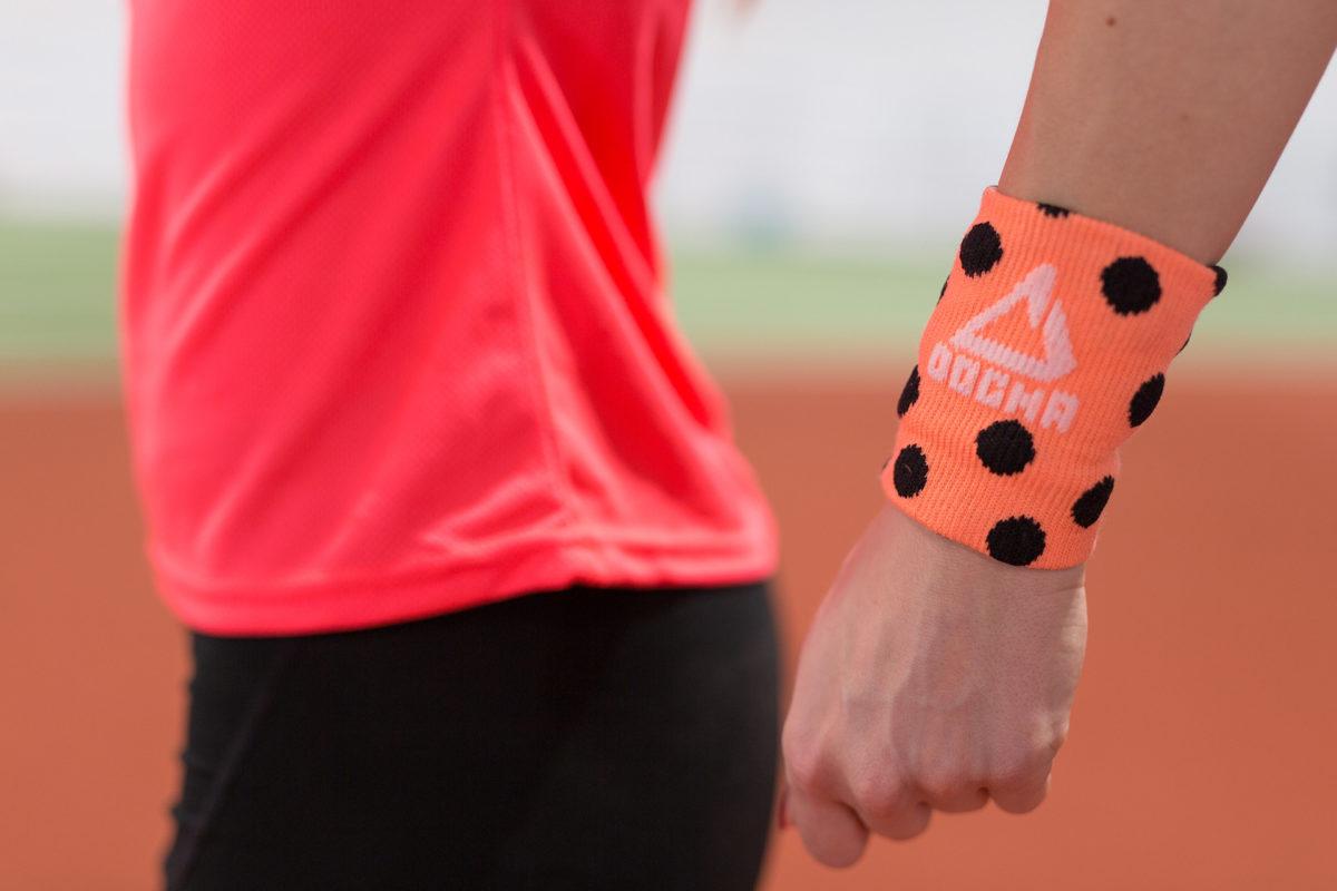Dogmasocks wrist sweat band woman orange close up picture of a hand