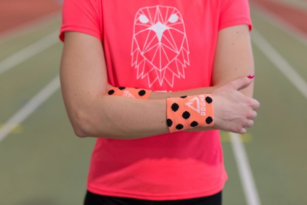 A picture of a girl wearing dogmasocks sweatbands on both hands in salmon with black dots.