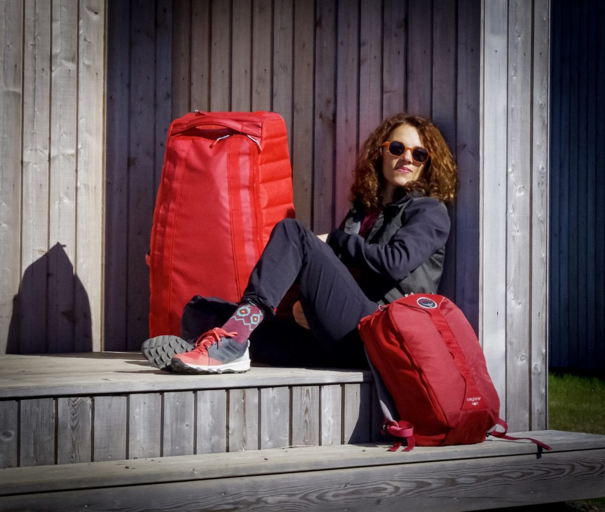 girl sitting on a porch of wooden cabin surrounded with luggage