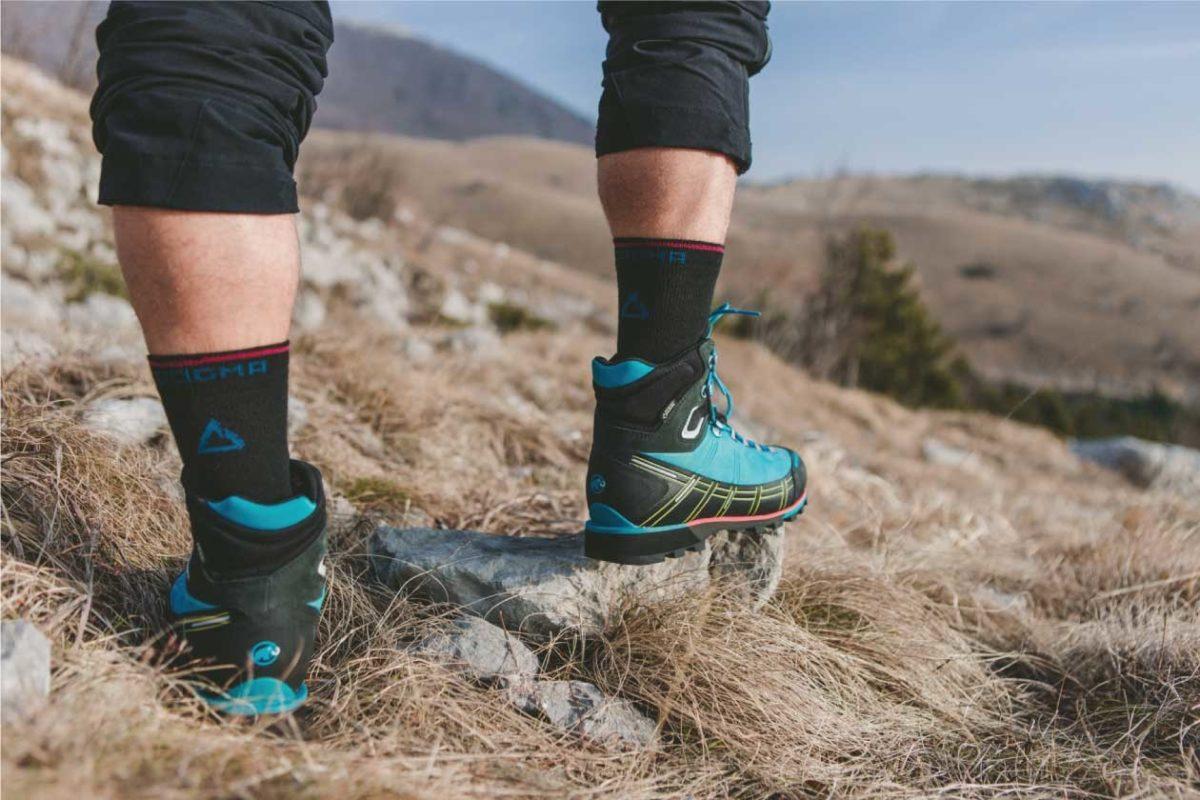A picture of a man wearing Dogma Yeti black hiking socks while hiking