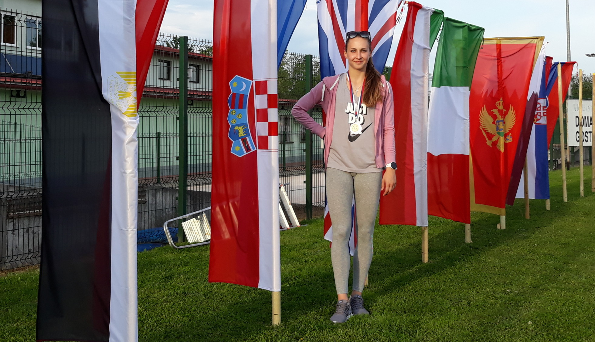 Megi in front of flags with her winning medal